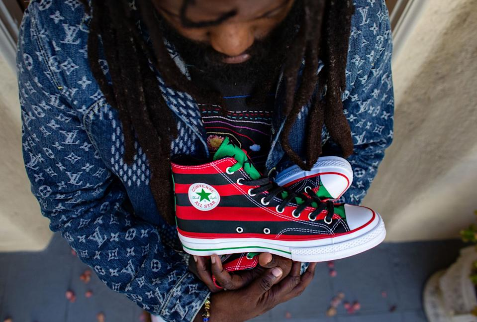 """Tremaine Emory with the sneakers he designed, inspired by the Pan-African flag. He says the sneaker, a collaboration with Converse, will drop in October and that marketing for the shoe will encourage voting in the November election. <span class=""""copyright"""">(Jason Armond / Los Angeles Times)</span>"""