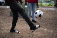 People play soccer at Las Raices camp in San Cristobal de la Laguna, in the Canary Island of Tenerife, Spain, Saturday, March 20, 2021. While Spain has been critical of its European neighbours' lack of solidarity when it comes to sharing the responsibility of migration, the country is similarly being criticized by migrants, authorities and human rights organizations on the Canary Islands where some 23,000 people arrived by sea last year and where many thousands remain on the island forcefully. (AP Photo/Joan Mateu)