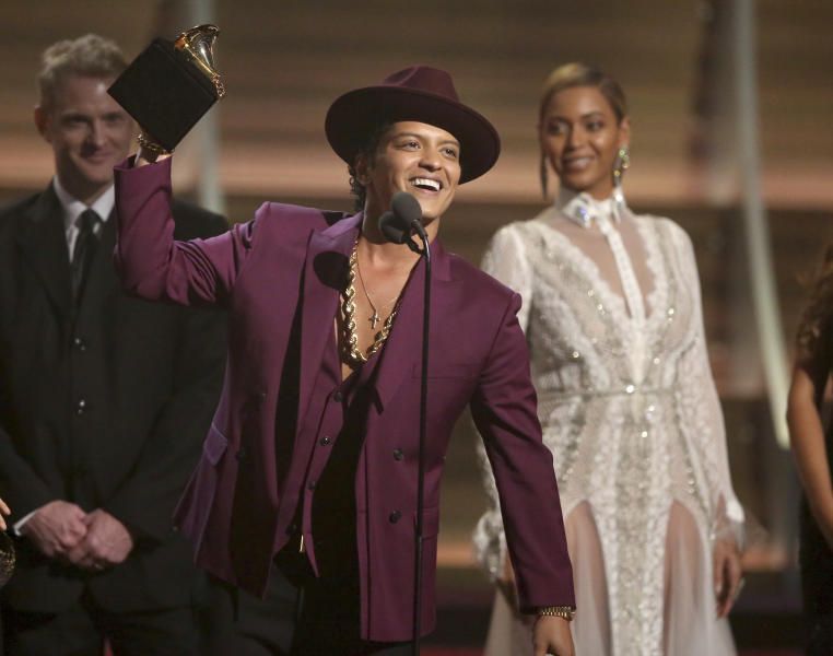 """FILE - In this Feb. 15, 2016 file photo, Bruno Mars accepts the award for record of the year for """"Uptown Funk"""" at the 58th annual Grammy Awards in Los Angeles. Mars, Justin Bieber and Britney Spears are set to perform during the 12-date """"Jingle Ball"""" tour this holiday season. IHeartMedia announced Tuesday, Oct. 11, that the tour will kick off Nov. 29 in Dallas and wrap Dec. 18 in Miami. (Photo by Matt Sayles/Invision/AP, File)"""