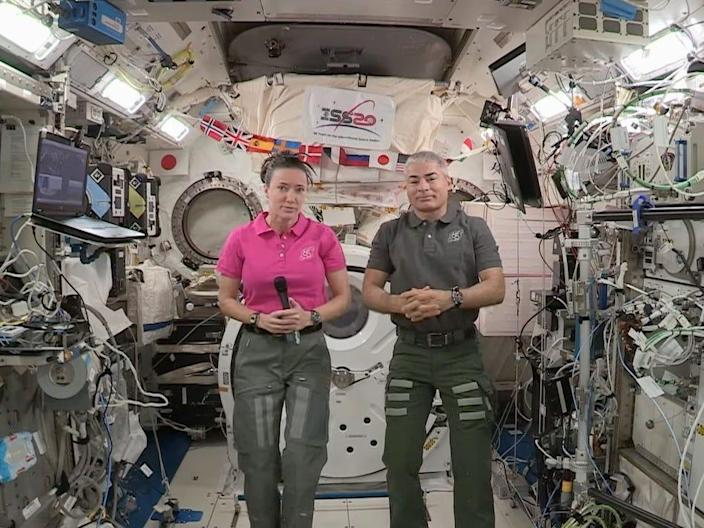 two astronauts holding microphone inside international space station