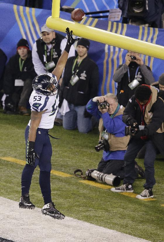 Seattle Seahawks' Malcolm Smith (53) celebrates after returning intercepting a pass for a touchdown during the first half of the NFL Super Bowl XLVIII football game against the Denver Broncos Sunday, Feb. 2, 2014, in East Rutherford, N.J. (AP Photo/Charlie Riedel)