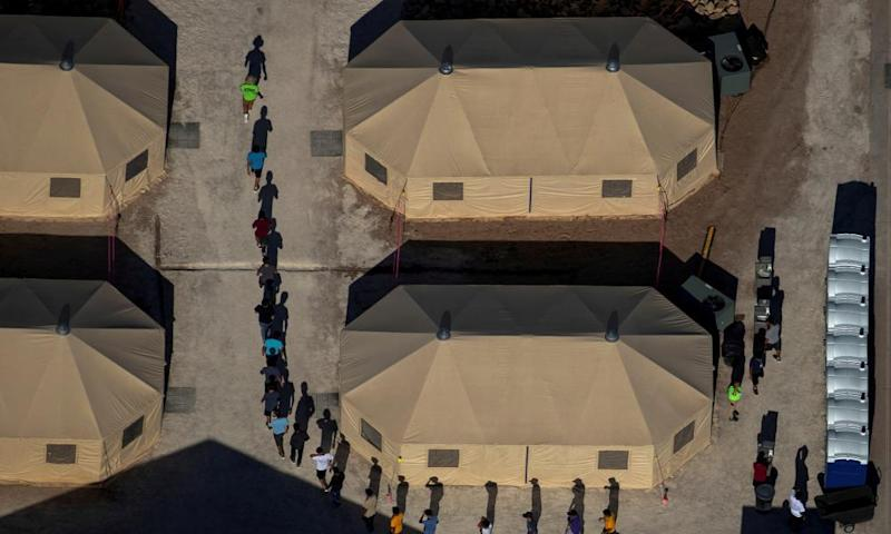 Migrant children are led by staff in single file between tents at a detention facility in Texas.