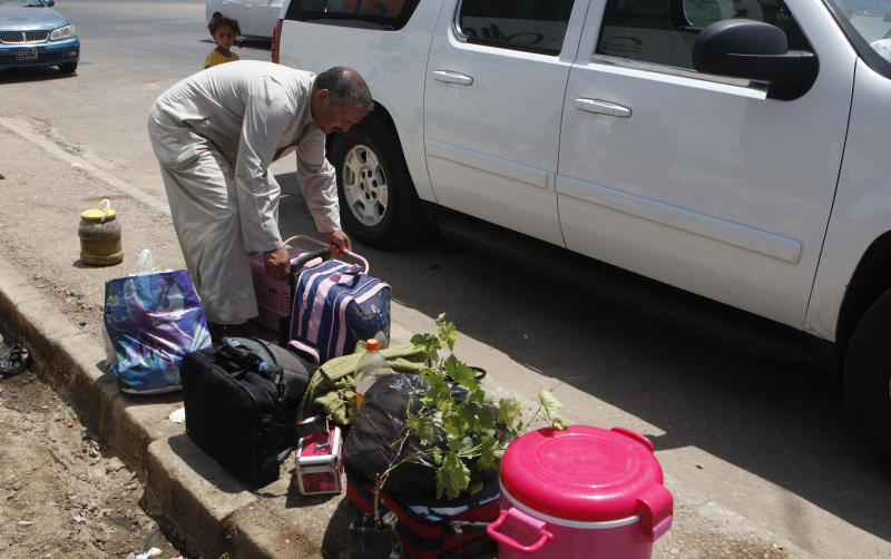 An Iraqi refugee who has just returned from Syria handles his family's luggage in the Mansour neighborhood of Baghdad, Iraq, Friday, July 20, 2012. Iraq has flown hundreds of its citizens out of Damascus to escape the civil war in Syria, an official said Friday, while thousands of Iraqis poured through a major border crossing despite rebel takeovers of Syrian government posts and escalating violence near the two nations' boundaries. (AP Photo/Karim Kadim)