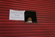 An employee waits on a customer via window service amid new lockdown restrictions due to the increase in COVID-19 infections, in Quito, Ecuador, Saturday, April 24, 2021. (AP Photo/Dolores Ochoa)