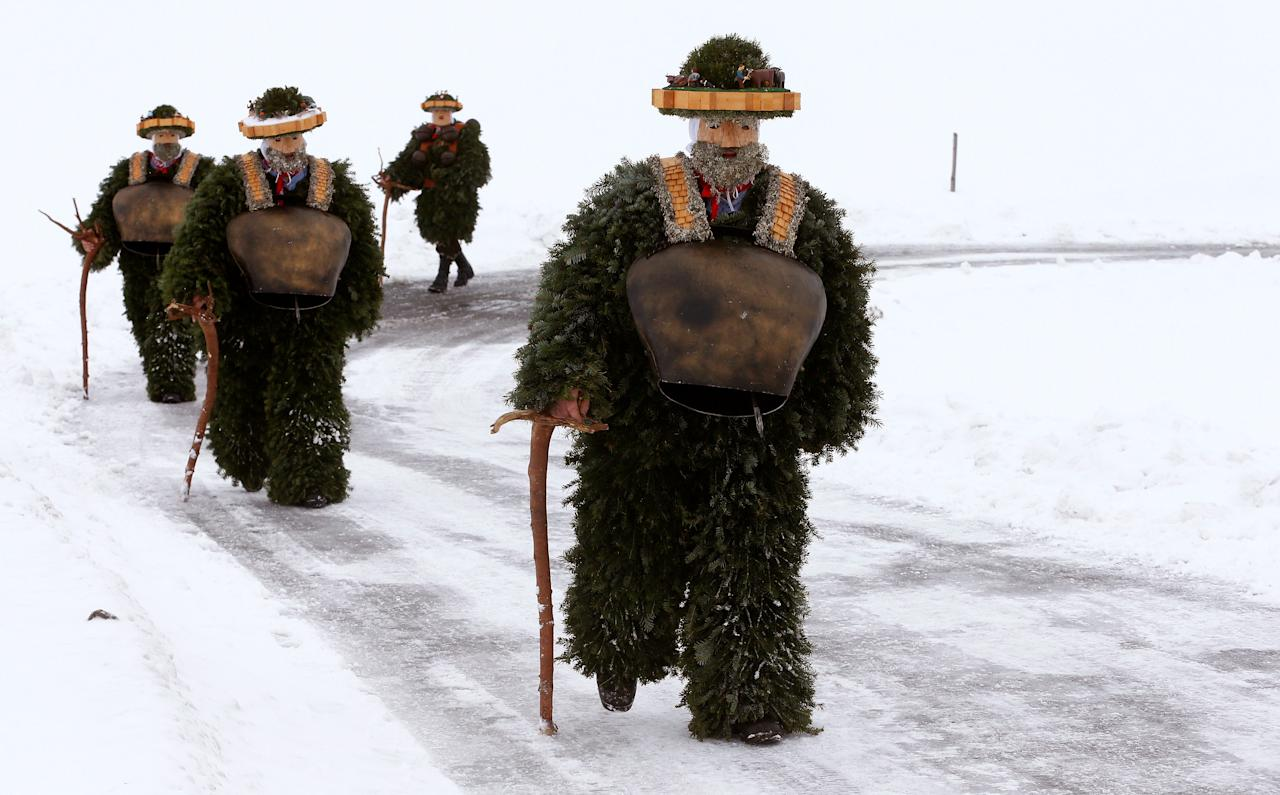 """Men dressed as """"Chlaeuse"""", figures that scare away evil spirits, carry round bells and cowbells as they walk on a partially snow-covered road during the traditional """"Sylvesterchlausen"""" near the northeastern village of Urnaesch, Switzerland January 13, 2017. REUTERS/Arnd Wiegmann      TPX IMAGES OF THE DAY"""