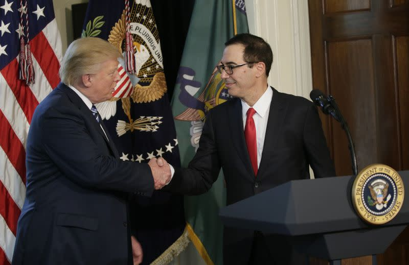 U.S. President Trump greets Treasury Secretary Mnuchin during signing financial services executive orders signing ceremony at the Treasury Department in Washington