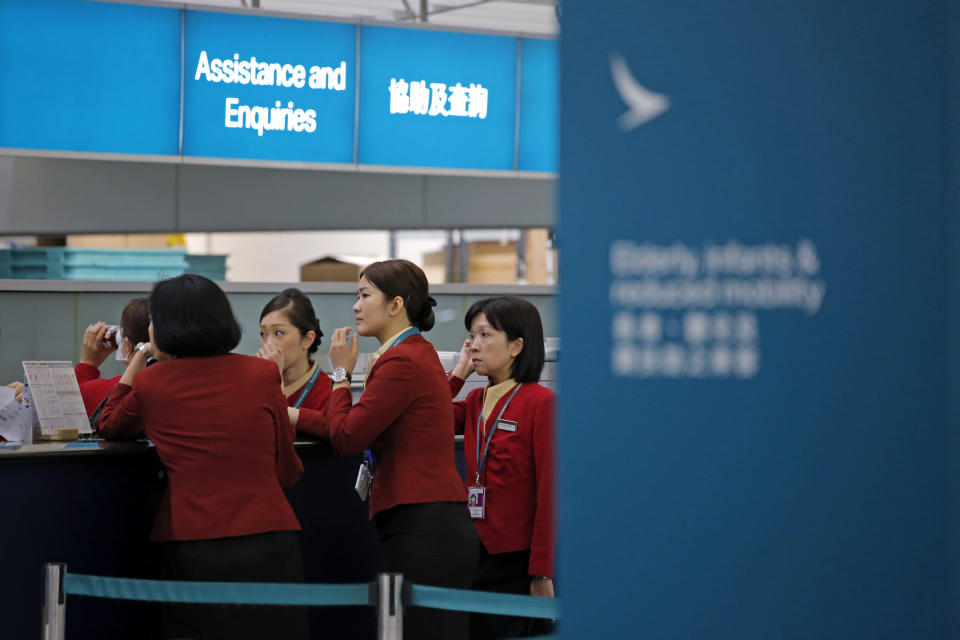 FILE - In this March 26, 2019 file photo, staff members chat at the check-in counter of Cathay Pacific Airways at the Hong Kong International Airport. Hong Kong airline Cathay Pacific Airways on Wednesday, Oct. 21, 2020, said it would cut 8,500 jobs and shut down its regional airline unit in a corporate restructuring, as it grapples with the plunge in air travel due to the pandemic. (AP Photo/Kin Cheung, File)