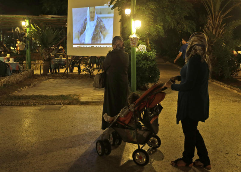 In this picture taken on Wednesday, July 24, 2013, two Syrian women watch one of the Syrian popular series Al-wiladah men al-khasira (Birth from the Waist), broadcast on a giant screen, left, at an outdoor coffee shop, in Beirut, Lebanon. Birth from the Waist is one of several Syrian soap operas airing during the Muslim holy month of Ramadan this year, almost all of them dealing with the Syrian civil war, now in its third year, spotlighting a conflict in which more than 100,000 people have been killed and millions of others uprooted from their homes. The series have captivated millions of viewers across the Arab world. (AP Photo/Hussein Malla)
