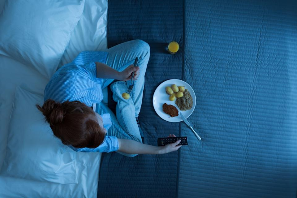 Photo from the top of young girl sitting on a bed, eating dinner and watching television
