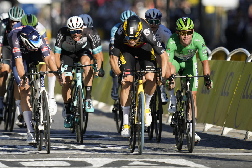 Britain's Mark Cavendish, wearing the best sprinter's green jersey, grimaces as Belgium's Wout Van Aert, center right, wins the sprint of the twenty-first and last stage of the Tour de France cycling race over 108.4 kilometers (67.4 miles) with start in Chatou and finish on the Champs Elysees in Paris, France,Sunday, July 18, 2021. (AP Photo/Christophe Ena)