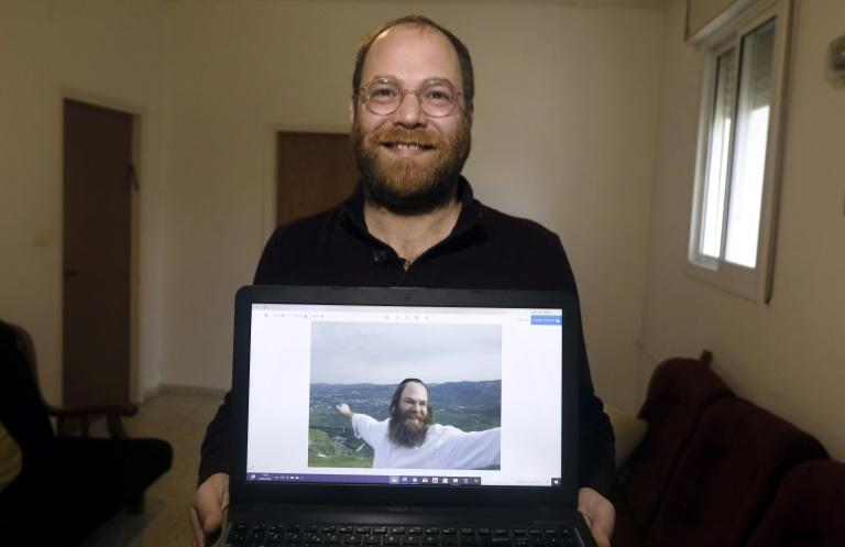 Avi Tfilinksi shows an old picture of himself as an observant ultra-Orthodox Jew at his apartment on the outskirts of Jerusalem (AFP Photo/MENAHEM KAHANA)