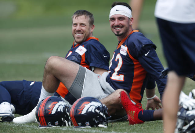 Denver Broncos quarterback Paxton Lynch, front, jokes with quarterback Case Keenum as they stretch before taking part in drills at the NFL football team's training camp Thursday, June 14, 2018, in Englewood, Colo. (AP Photo/David Zalubowski)