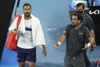Italy's Fabio Fognini, right, speaks as compatriot Salvatore Caruso walks away after their second round match at the Australian Open tennis championship in Melbourne, Australia, Thursday, Feb. 11, 2021. Fognini won the match. (AP Photo/Hamish Blair)
