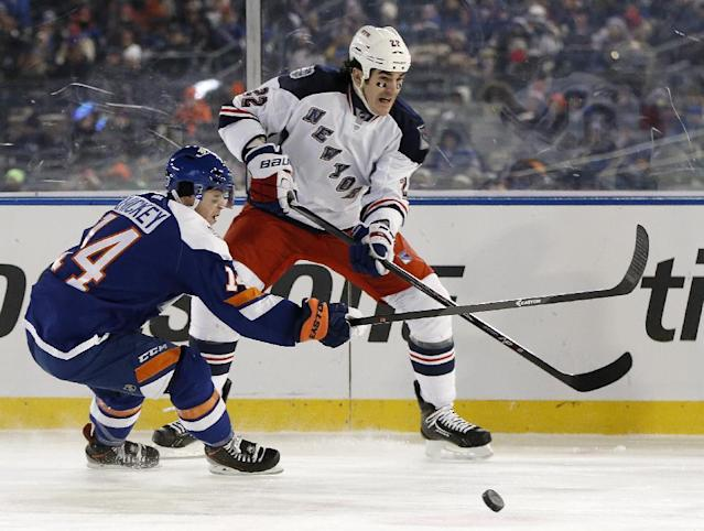 New York Islanders defenseman Thomas Hickey (14) defends New York Rangers center Brian Boyle (22) during the second period of an NHL hockey game at Yankee Stadium in New York, Wednesday, Jan. 29, 2014. The Rangers won 2-1. (AP Photo/Kathy Willens)