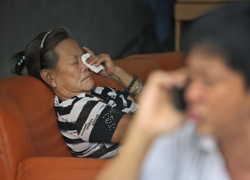"Suwarni the mother of Sugianto Lo, who was onboard the Malaysia Airlines plane MH370 with his wife Vinny, weeps as an unidentified relative makes a phone call at her residence in Medan, North Sumatra, Indonesia, Tuesday, March 25, 2014. After 17 days of desperation and doubt over the missing Malaysia Airlines jet, the country's officials said an analysis of satellite data points to a ""heartbreaking"" conclusion: Flight 370 met its end in the southern reaches of the Indian Ocean, and none of those aboard survived. (AP Photo/Binsar Bakkara)"