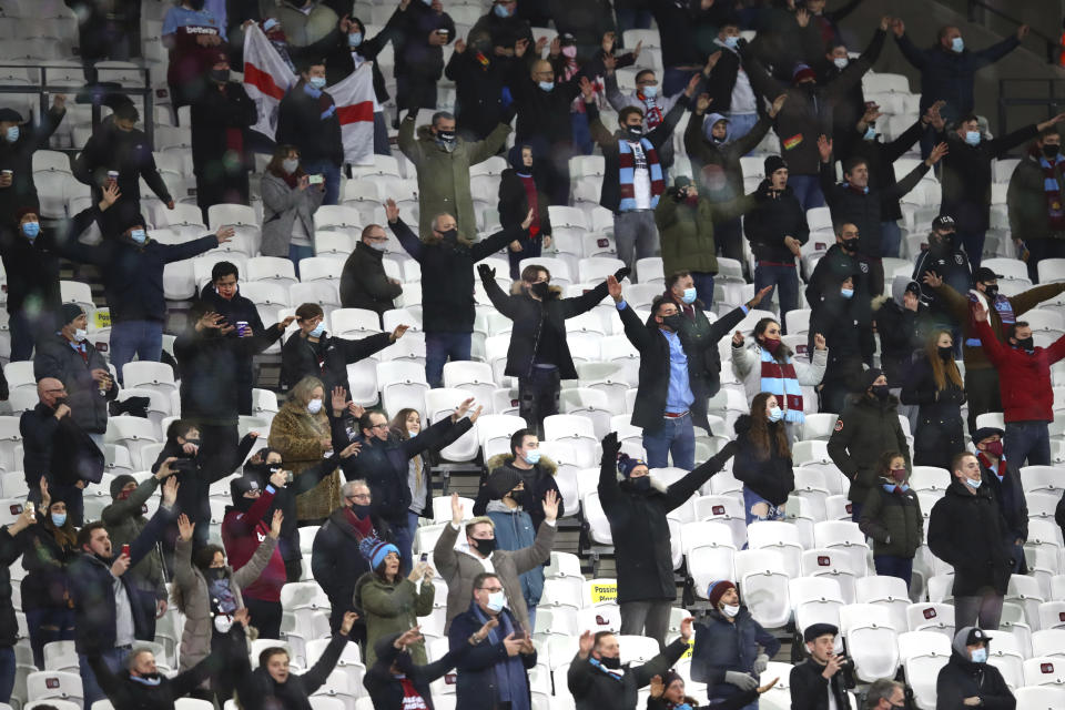 Fans stand and cheer as they are socially distanced during the English Premier League soccer match between West Ham United and Manchester United at the London stadium in London, England, Saturday, Dec. 5, 2020. (Julian Finney/Pool Via AP)