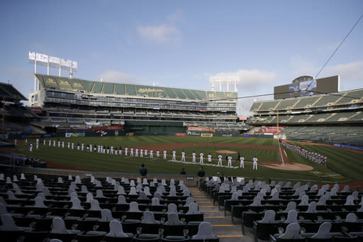 Players and coaches from the Oakland Athletics and the Los Angeles Angels hold a black ribbon in honor of the Black Lives Matter movement before the teams played a baseball game in Oakland, Calif., Friday, July 24, 2020. (AP Photo/Jeff Chiu)