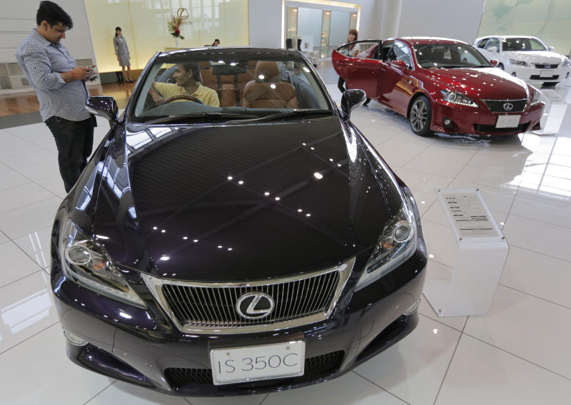 """Visitors look at """"Lexus"""" IS350C displayed at a Toyota's showroom in Tokyo, Friday, Aug. 3, 2012. Toyota says April-June profit zoomed to 290.3 billion yen ($3.7 billion) from 1.1 billion yen on a jump in global sales as the Japanese automaker makes a comeback from a disaster plagued 2011. (AP Photo/Itsuo Inouye)"""