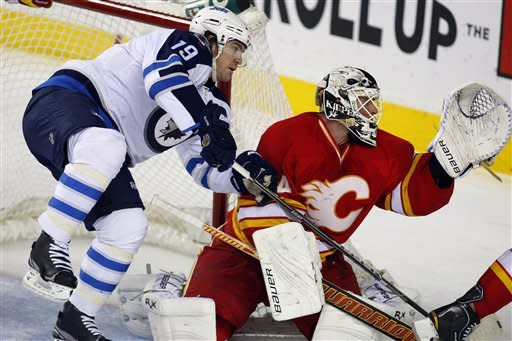 Winnipeg Jets' Jim Slater, left, stumbles into Calgary Flames goalie Miikka Kiprusoff, from Finland, during the second period of an NHL hockey game in Calgary, Alberta, Friday, March 9, 2012. (AP Photo/The Canadian Press, Jeff McIntosh)
