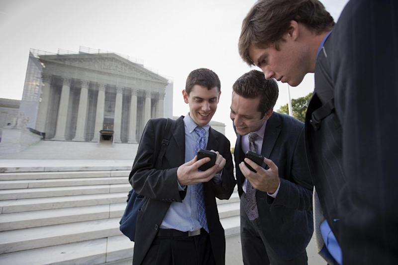 After delivering coffee to visitors to waiting to enter the Supreme Court, SCOTUS Blog interns check their smartphones for updates on the latest news as outside the court in Washington, Wednesday, June 26, 2013, as the justices are expected to hand down major rulings on two gay marriage cases that could impact same-sex couples across the country. From left to right are Dan Stein, Max Mallory, and Andrew Hamm. (AP Photo/J. Scott Applewhite)