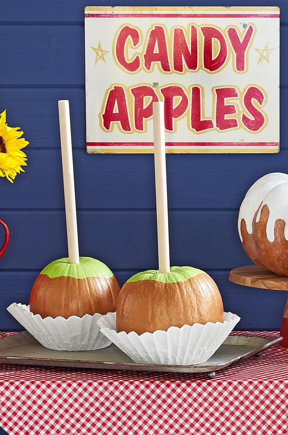 """<p>Although these painted pumpkins look just like real <a href=""""https://www.countryliving.com/food-drinks/g975/apple-dessert-recipes/"""" rel=""""nofollow noopener"""" target=""""_blank"""" data-ylk=""""slk:candied apples"""" class=""""link rapid-noclick-resp"""">candied apples</a>, they unfortunately don't have the delicious taste. To make this sweet craft, first remove the stem of a medium pumpkin. Use craft paint to paint the top part green, so it resembles a Granny Smith apple. Once dry, use craft paint to paint the bottom 2/3 a golden caramel color. (Are you drooling yet?) Then, hot-glue a 3/4- by 12-inch dowel where the stem was. Display in a large, industrial-size coffee filter. </p>"""