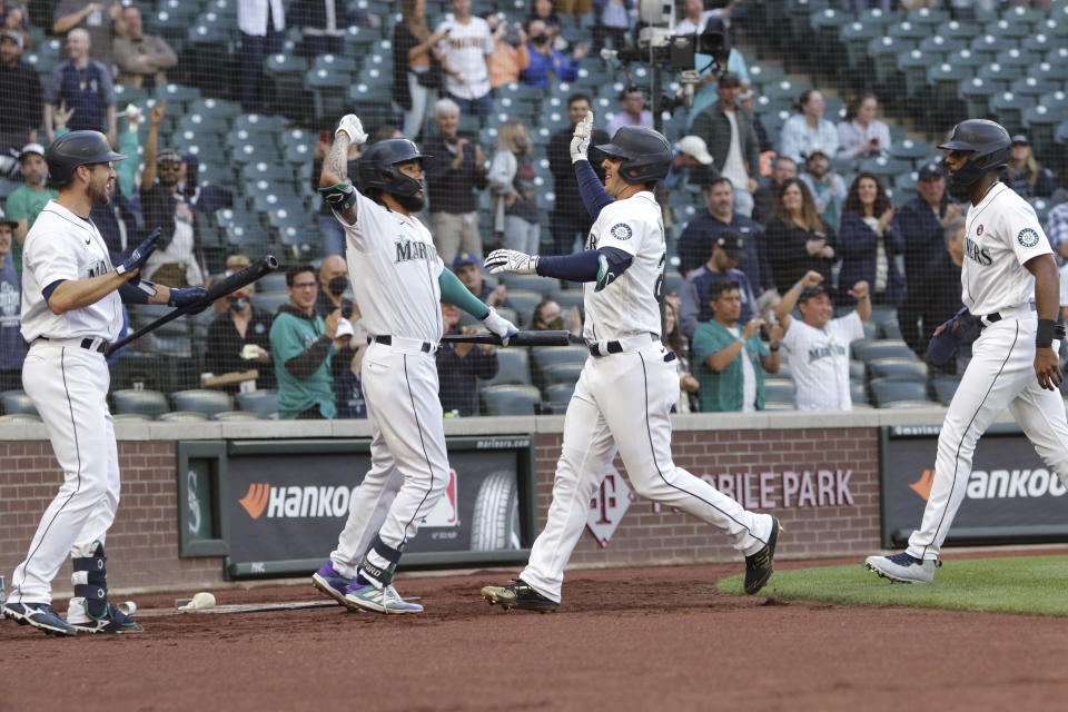 Seattle Mariners' Dylan Moore, second from right, celebrates with Tom Murphy, J.P. Crawford and Kyle Lewis, from left, after Moore's three-run home run during the fourth inning of the team's baseball game against the Cleveland Indians, Saturday, May 15, 2021, in Seattle. (AP Photo/Jason Redmond)
