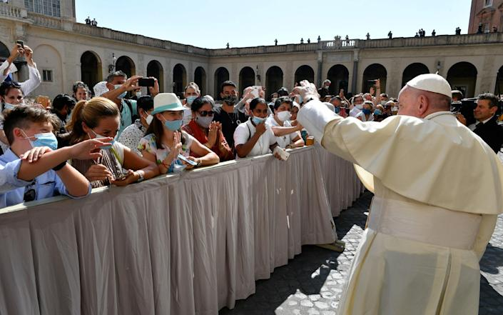 Pope Francis receives waves to the faithful at the San Damaso courtyard during the weekly general audience at the Vatican - Vatican via Reuters