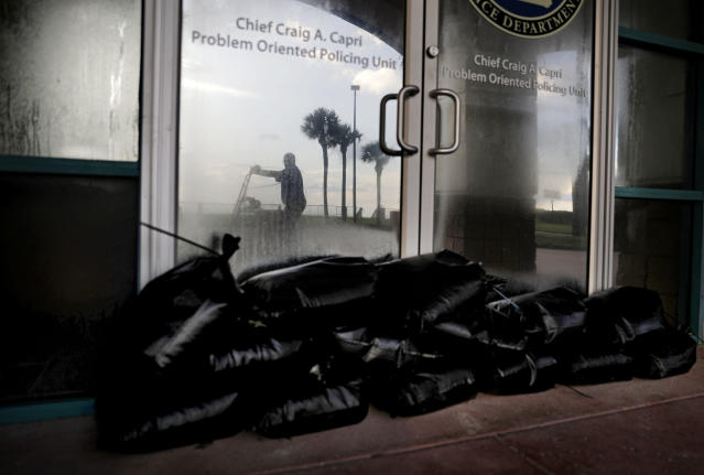 <p>Sandbags sit outside a police station office as a worker secures the grounds of a hotel along the beach ahead of Hurricane Irma in Daytona Beach, Fla., Friday, Sept. 8, 2017. (Photo: David Goldman/AP) </p>