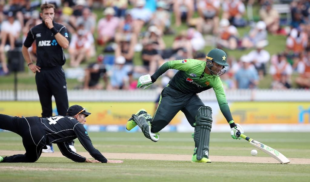 New Zealand's Mitchell Santner (L) is unable to run out Pakistan's Fakhar Zaman (R) during the fourth one-day international match in Hamilton (AFP Photo/MICHAEL BRADLEY)