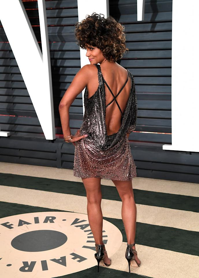 <p>The actress turned to Atelier Versace for her disco-inspired, backless mini dress. The 50-year-old finished her look with an epic afro. [Photo: PA] </p>