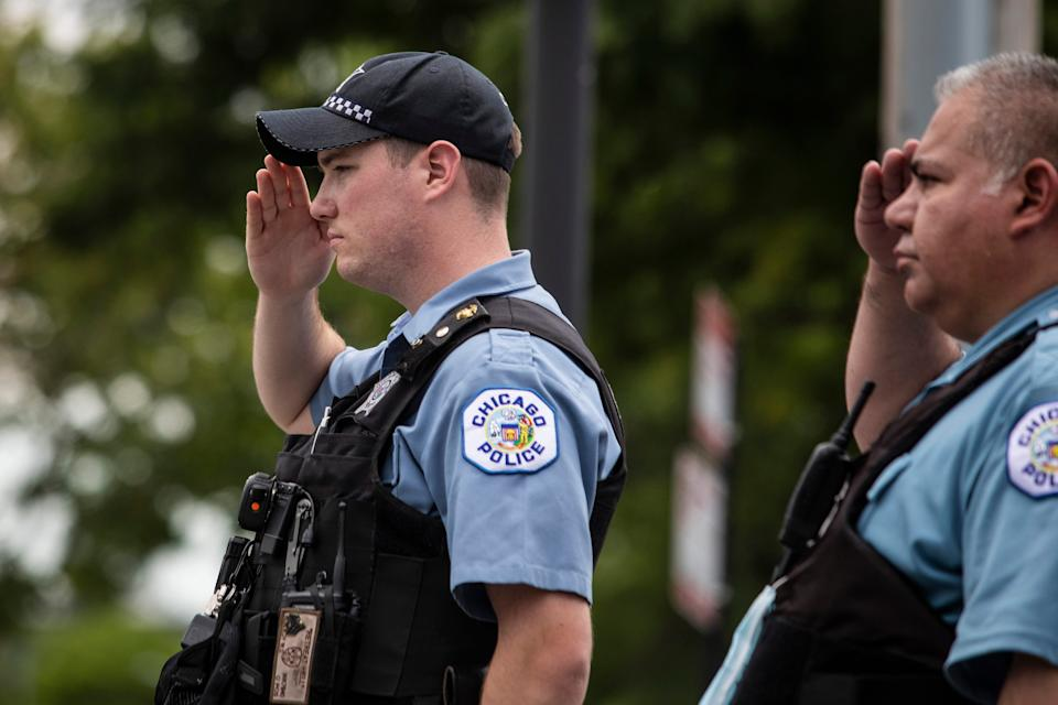 Officers salute outside the Cook County Medical Examiner's Office as an ambulance passes, containing the body of a Chicago Police officer, Tuesday, July 28, 2020, in Chicago.