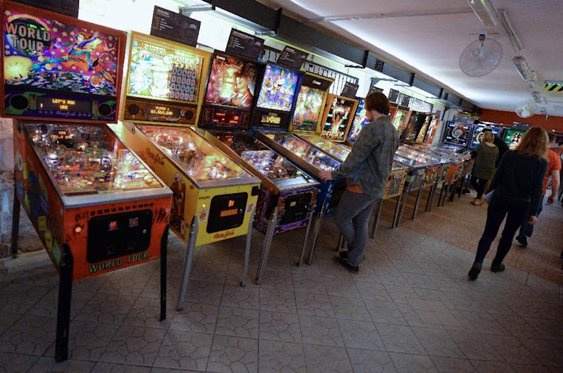 Visitors play in the 'Pinball Museum' in Budapest on March 14, 2015 (AFP Photo/Attila Kisbenedek)