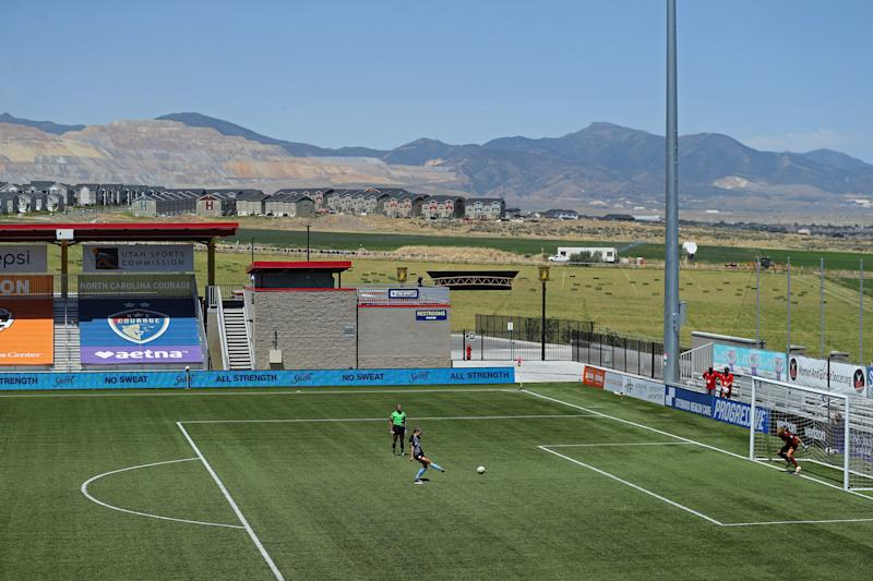 Sky Blue FC's Sarah Killion kicks a penalty against Washington Spirit's Aubrey Bledsoe with the mountains and green landscape in the background.