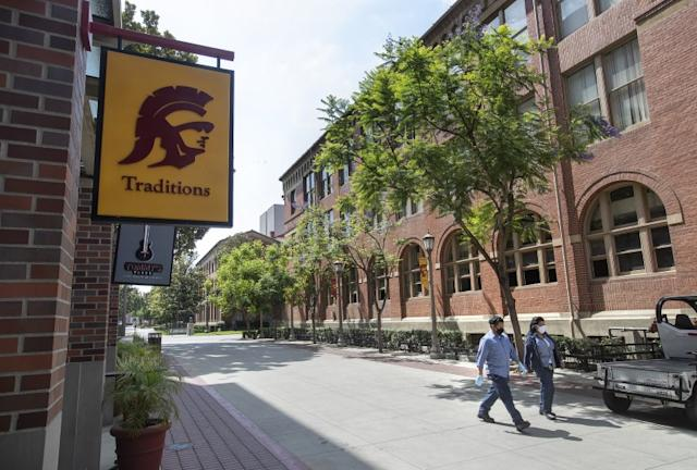 """Workers make their way on the campus of USC in Los Angeles. <span class=""""copyright"""">(Mel Melcon / Los Angeles Times)</span>"""