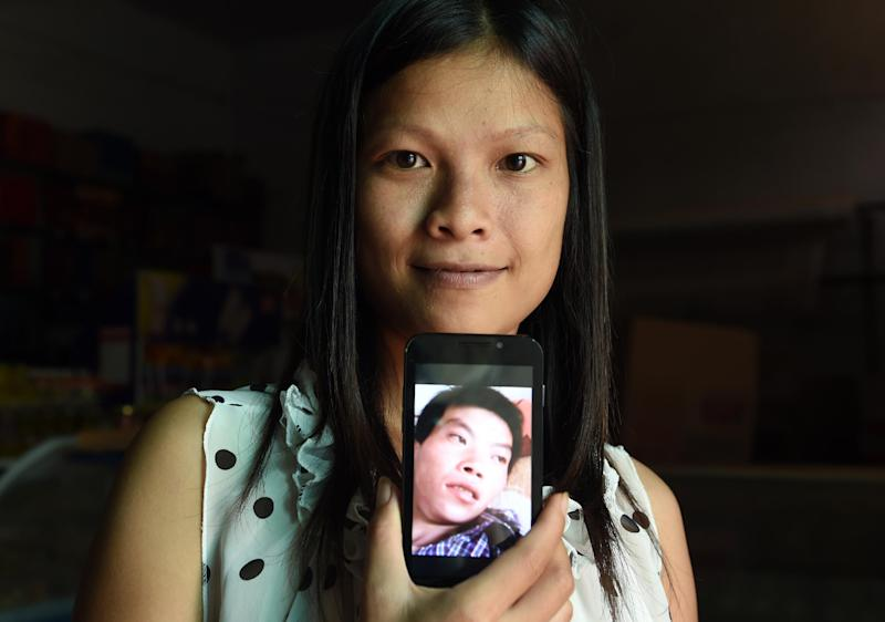 Vietnamese bride Vu Thi Hong Thuy poses with a photo of her Chinese husband in Weijian village, China's Henan province on July 30, 2014 (AFP Photo/Greg Baker)