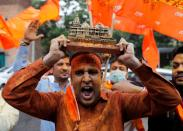 A supporter of ruling Bharatiya Janata Party (BJP) holds a model of proposed Ram Temple in Ayodhya as they celebrate the stone laying ceremony, in New Delhi