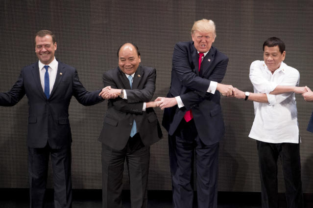 "<p>U.S. President Donald Trump, second from right, reacts as he does the ""ASEAN-way handshake"" with Russian Prime Minister Dmitry Medvedev, left, Vietnamese Prime Minister Nguyen Xuan Phuc, second from left, and Philippine President Rodrigo Duterte on stage during the opening ceremony at the ASEAN Summit at the Cultural Center of the Philippines, Nov. 13, 2017, in Manila, Philippines. Trump initially did the handshake incorrectly. Trump is on a five-country trip through Asia traveling to Japan, South Korea, China, Vietnam and the Philippines. (Photo: Andrew Harnik/AP) </p>"