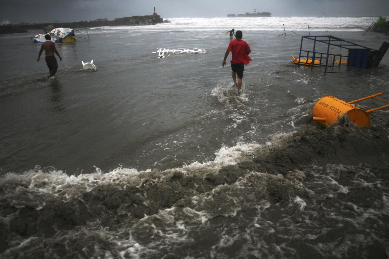Vendors that were caught unprepared try to recover their belongings after high waves dragged their beach stalls into the sea in Veracruz, Mexico, Thursday Aug. 9, 2012. Tropical Storm Ernesto headed into Mexico's southern Gulf coast as authorities in the flood-prone region prepared shelters, army troops and rescue personnel for drenching rains. (AP Photo/Felix Marquez)