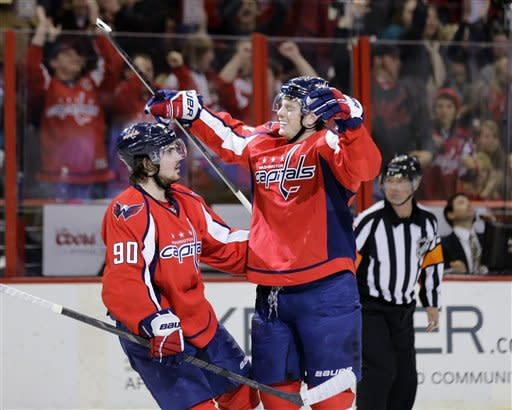 Washington Capitals center Marcus Johansson (90), from Sweden, comes in to celebrate with defenseman John Carlson, after Carlson's goal in the second period of an NHL hockey game against the New York Islanders on Tuesday, March 26, 2013, in Washington. (AP Photo/Alex Brandon)