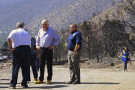 Nevada Gov. Steve Sisolak, second from left, tours areas of the forest damaged by wildfires near where the Tamarack Fire ignited earlier in July in Gardnerville, Nev., Wednesday, July 28, 2021. The governors of California and Nevada are calling for increased federal assistance as they tour an area blackened by one of several massive wildfires that have destroyed dozens of homes. Wednesday's tour of the Tamarack Fire along the state line comes as numerous wildfires char land and homes in a dozen states. (AP Photo/Sam Metz)