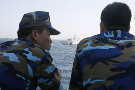 Officers of the Vietnamese Marine Guard talk as they monitor a Chinese coast guard vessel on the South China Sea, about 210 km (130 miles) offshore of Vietnam