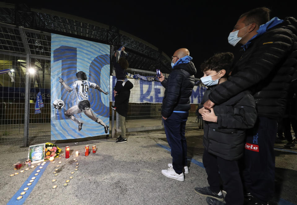 SAN PAOLO STADIUM, NAPOLI, CAMPANIA, ITALY - 2020/11/25: People outside San Paolo Stadium in front of a drawing depicting Diego Armando Maradona with candles in front of him. (Photo by Carmine Laporta/KONTROLAB/LightRocket via Getty Images)