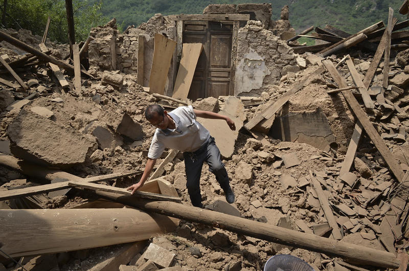 A man checks a destroyed house following an earthquake which hit Luozehe town in Yiliang county in southwest China's Yunnan province Saturday, Sept. 8, 2012. Authorities poured aid into a remote mountainous area of southwestern China and rescue workers with sniffer dogs searched for survivors Saturday after twin earthquakes killed at least 80 people. (AP Photo) CHINA OUT