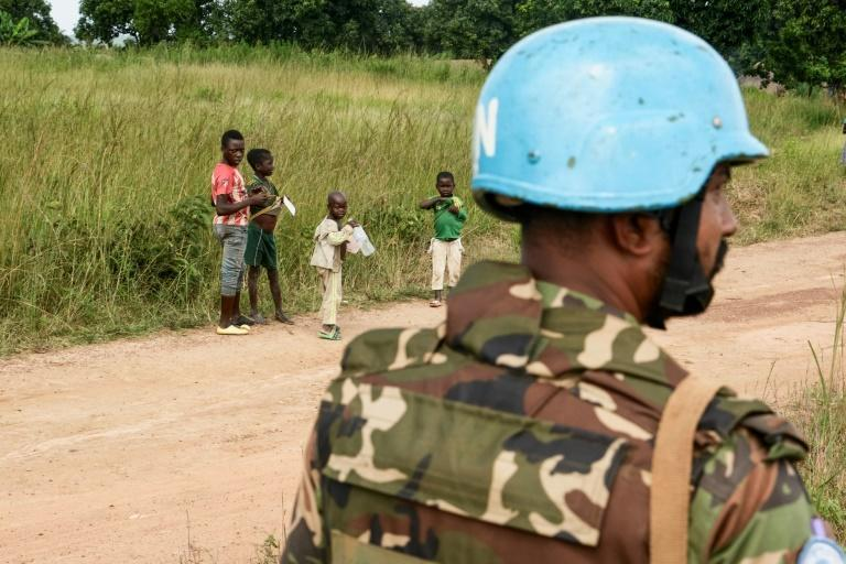 Children look at a United Nations Bangladeshi soldier, part of the MINUSCA peacekeeping force in the Central African Republic