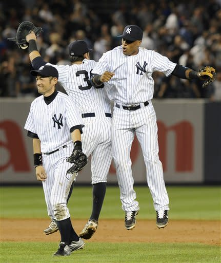 New York Yankees' Ichiro Suzuki, Nick Swisher (33) and Robinson Cano celebrate their 6-4 win over the Boston Red Sox in a baseball game on Friday, Aug., 17, 2012, at Yankee Stadium in New York. Swisher hit two solo home runs during the game. (AP Photo/Kathy Kmonicek)