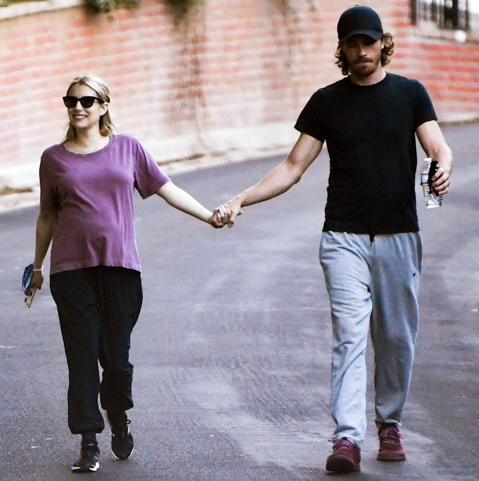 <p>Parents-to-be Emma Roberts and Garrett Hedlund hold hands as they go on a walk through L.A. on Sunday.</p>