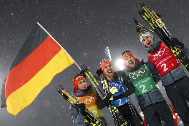 Nordic Combined Events - Pyeongchang 2018 Winter Olympics - Men's Team 4 x 5 km Final - Alpensia Cross-Country Skiing Centre - Pyeongchang, South Korea - February 22, 2018 - Johannes Rydzek of Germany holds the German flag as he celebrates winning the gold medal with teammates Vinzenz Geiger, Fabian Riessle and Eric Frenzel. REUTERS/Kai Pfaffenbach
