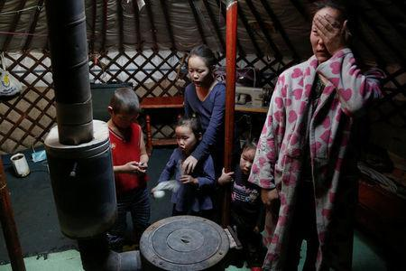 The wife and children of Setevdorj Myagmartsogt gather around their new coal burning stove while talking to reporters in their tent-like ger home in Ulaanbaatar, Mongolia January 29, 2017. Setevdorj Myagmartsogt, a part time worker at coal packing shop, lives with his wife, four kids and two relatives in their ger home near a coal depot not far from the city centre. REUTERS/B. Rentsendorj