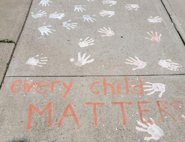 Kimberly Garrod and her neighbour used chalk to make dozens of handprints on their Hamilton, Ont., sidewalk Wednesday night in support of Indigenous communities following recent discoveries of unmarked graves at the sites of former residential schools. (Submitted by Kimberly Garrod - image credit)