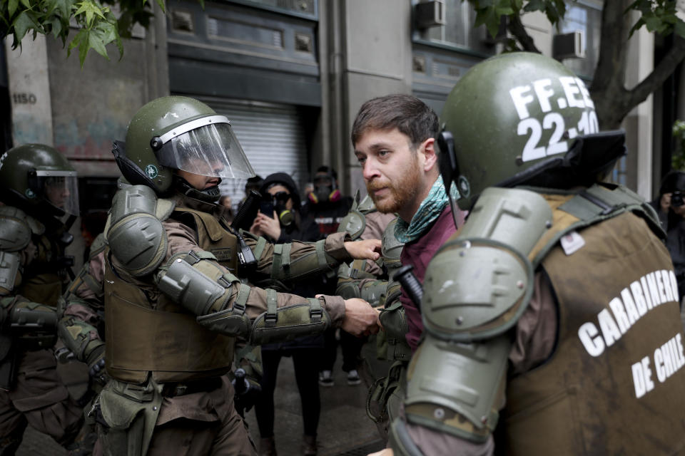 Riot police detain an anti-government demonstrators in front of La Moneda presidential palace in Santiago, Chile, Friday, Nov. 1, 2019. Groups of Chileans continued to protests as government and opposition leaders debated the response to nearly two weeks of protests that have paralyzed much of the capital and forced the cancellation of two major international summits. (AP Photo/Rodrigo Abd)